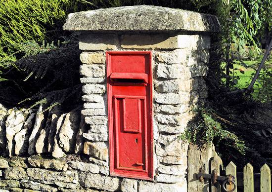 postbox in wall outside house in village